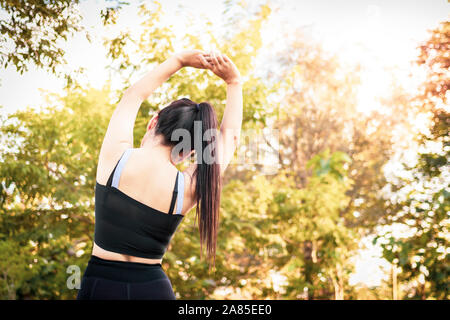 Beautiful woman doing stretching exercises on the floor.Young sportive woman doing exercising in summer park.