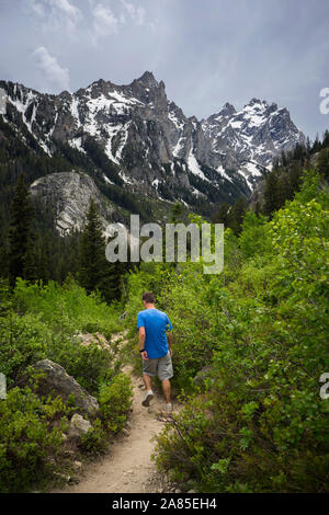 Man hiking on a trail in the Teton mountains in the summer - Stock Photo