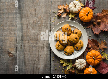 Pumpkin chocolate chip cookies on a plate with fall decor from above. - Stock Photo