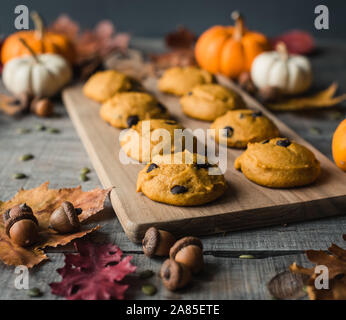 Close up of pumpkin chocolate chip cookies on a wooden board. - Stock Photo