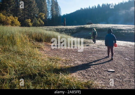 Two children hiking in meadow during a cold morning - Stock Photo