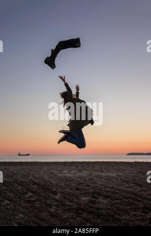 Young woman is jumping in the beach at sunset. Lifestyle, freedom - Stock Photo