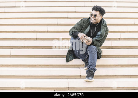 young black man with sunglasses in casual modern clothes sitting on stairs, listen to music of his phone in earphones while smile, technology and life - Stock Photo