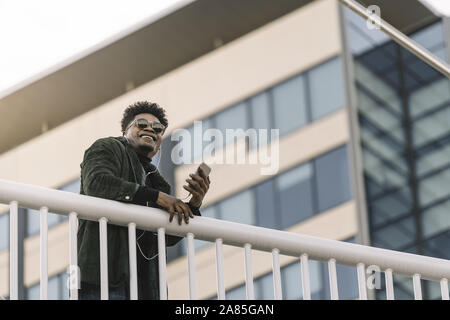 portrait of a smiling young black man with sunglasses listening to music with earphones and mobile phone while leaning on a handrail outdoors in the c - Stock Photo