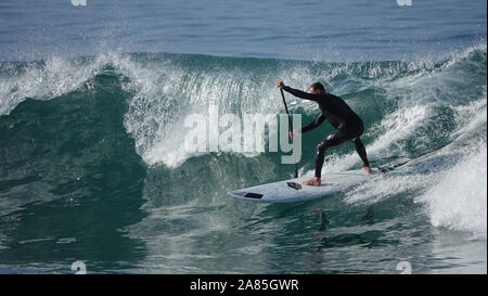 Athletic man (52 year old Caucasian) stays fit and active surfing on a SUP (stand up paddle board) - Stock Photo