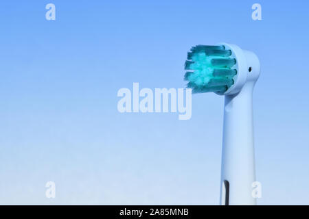 Electric toothbrush in closeup against light blue gradient background, copy space. Dental hygiene concept, puristic background for dentist surgery. - Stock Photo