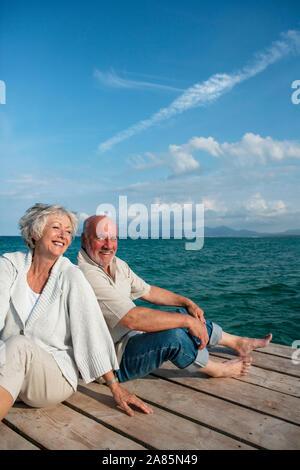 Senior couple sitting on a pier - Stock Photo