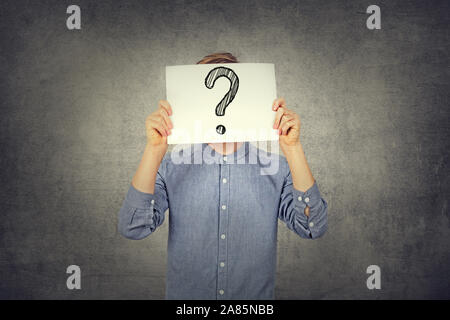 Tennager Boy using a white paper with drawn question mark on gray wall background. Question mark, symbol. Pensive male. Getting answers. Doubtful man - Stock Photo