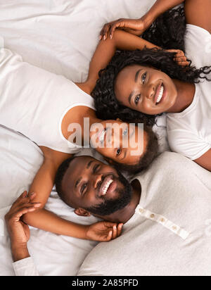 Top view of happy black family lying in bed together - Stock Photo