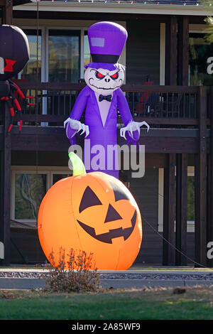 A blow up pumpkin and goblin decorate a house in Bend, Oregon, on Halloween. - Stock Photo