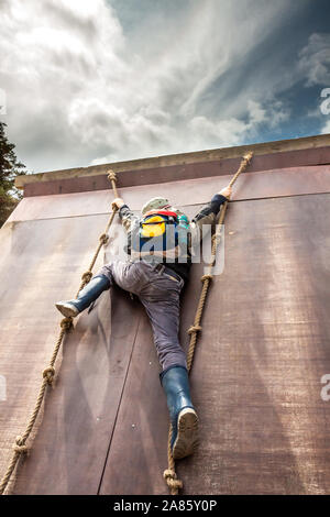 Young boy in wellys climbing up a wall with ropes.