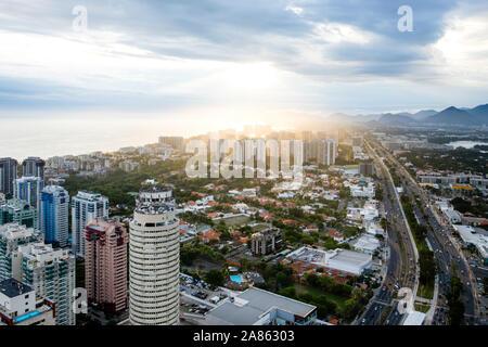 Sunlight breaking through clouds over cityscape of Rio de Janeiro - Stock Photo