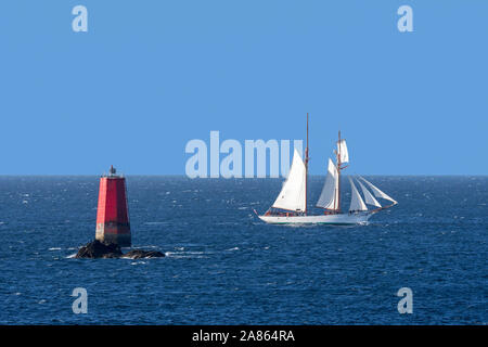 Sailing ship passing red sea mark / seamark / navigation mark on the shallows Les Vieux Moines at Pointe Saint-Mathieu, Finistère, Brittany, France - Stock Photo