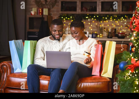 Afro couple buying gifts online, using laptop and credit card - Stock Photo