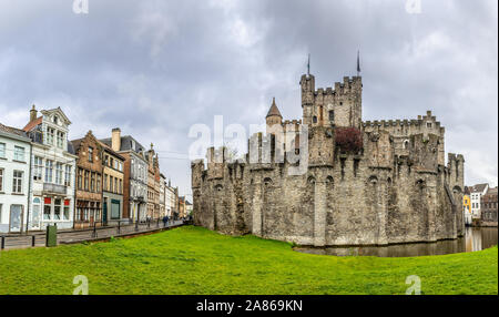 Fortified walls and towers of Gravensteen medieval castle with moat in the foreground, Ghent East Flanders, Belgium