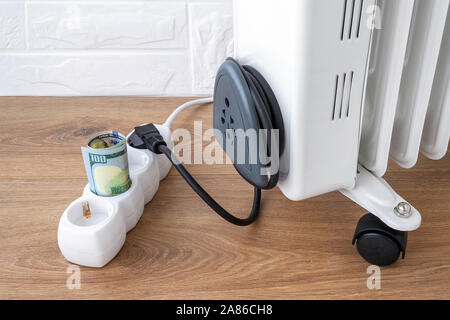 One hundred dollar bill in extension cord near electric oil heater plug. Expensive electricity and higher electricity costs during winter concept. - Stock Photo