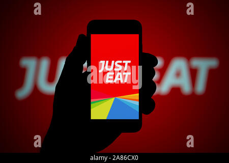 A man looks at his iPhone which displays the Just Eat logo, with the same logo in the background (Editorial use only). - Stock Photo
