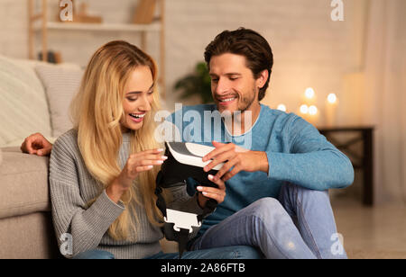 Boyfriend Giving VR Headset To Happy Girlfriend At Home - Stock Photo