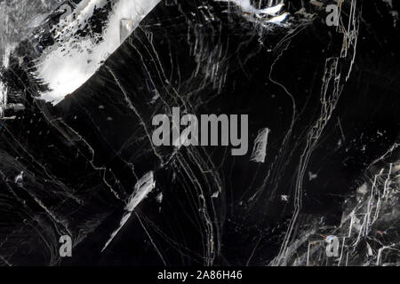 Thin layer of broken ice against black. Textured abstract background with reflections.