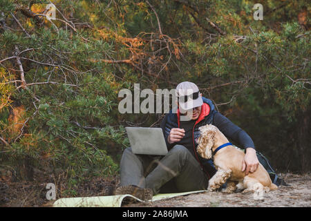 Experienced traveler use laptop with friend pet during walking jorney in forest. Man hugs a dog - Stock Photo