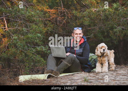 Experienced traveler use laptop with friend pet during walking jorney in forest. Smiling man and dog are looking at the camera. - Stock Photo