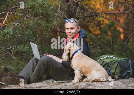 Experienced traveler use laptop with friend pet during walking jorney in forest. Man is looking at camera. - Stock Photo