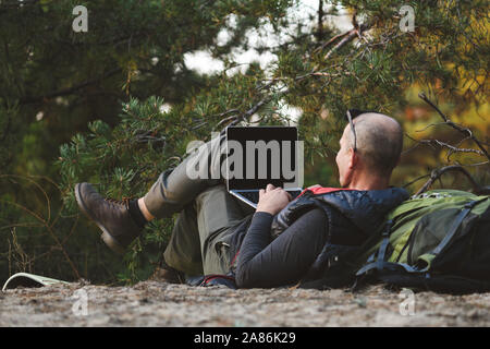 Elderly stylish man tourist use laptop in forest. Back view, male hiker lying on back leaning on backpack, with laptop computer, typing, blogging, bro - Stock Photo