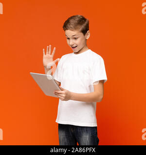 Friendly teen boy conferencing on digital tablet - Stock Photo