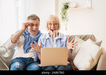 Win lottery. Surprised mature couple winning online auction bid - Stock Photo