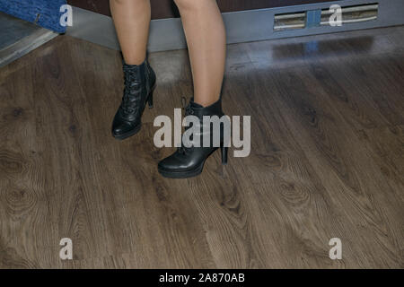 Lose-up pair of woman legs in black lace-up boots on laminated floor background. - Stock Photo