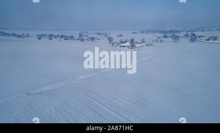 Aerial View of Fresh Followed Morning Snow over an Amish Countryside and Farm Land as Seen by a Drone - Stock Photo
