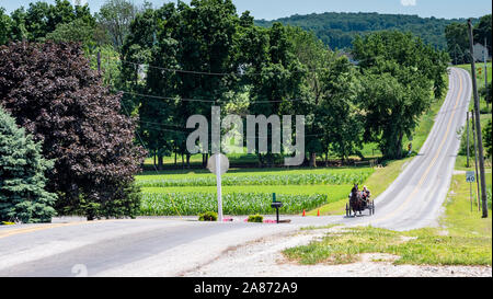 Lancaster, Pennsylvania, June 2019 - Amish Open Family Horse and Buggy Out for a Stroll on a Sunny Sunday in the Countryside - Stock Photo