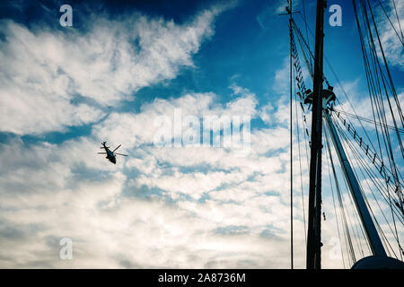 Valencia, Spain - November 2, 2019: Rescue helicopter flying over a sailboat, seen from the sea. - Stock Photo
