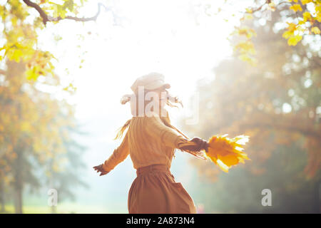 Hello autumn. smiling young woman in sweater, skirt, hat, gloves and scarf with yellow leaves having fun time outside in the autumn park. - Stock Photo