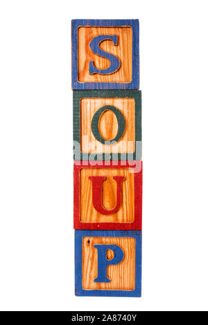 The food word soup spelled out with old toy wooden blocks on a white background. - Stock Photo