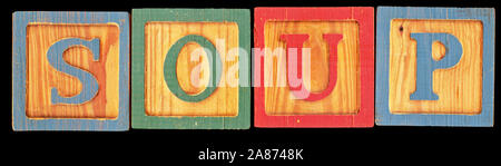 High resolution scan of old toy wooden blocks spelling out the word SOUP. This is isolated on a black background. - Stock Photo