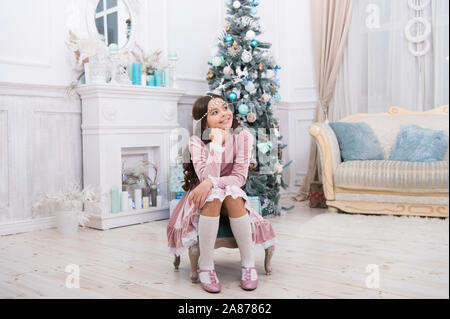 Making wish. Waiting for Santa claus. Adorable girl making wish near christmas tree decorated interior. Hopeful child. New year eve. Dreams come true. Hope concept. Dreamy baby christmas wish. - Stock Photo