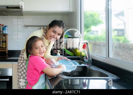 Beautiful Asian mother and daughter having fun while washing dishes together with detergent on sink in kitchen at home. Happy family time to teaching - Stock Photo