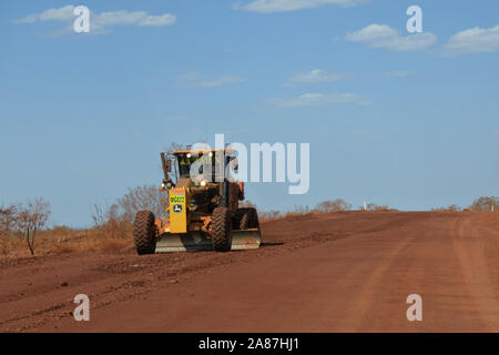 Motor Grader flatting a dirt road surface in Western Australia,one of the largest geographically-spread road system in the w - Stock Photo