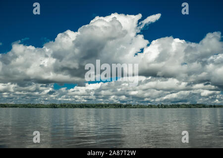 Big white clouds on the blue sky above the river