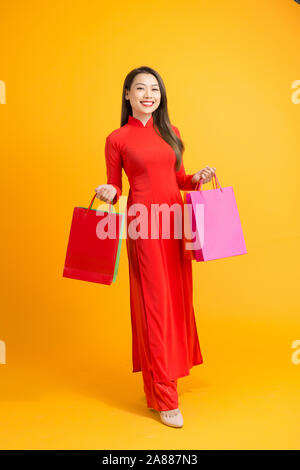 Vietnamese woman wearing traditional ao dai clothes and holding shopping bags in Tet festival on white background - Stock Photo