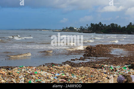 Sea Pollution: Garbage dumped in the Sri Lankan Sea near Colombo. women collects plastic things in a pile of garbage brought by the surf from the sea - Stock Photo