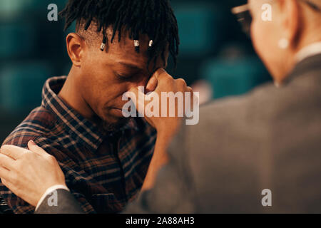 Sad African young man crying and telling about his problems to the woman who supporting him