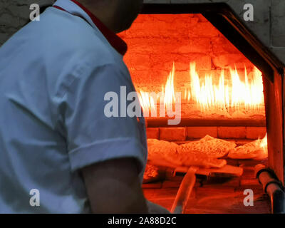Baking bread in a traditional way in a turkish restaurant - Stock Photo