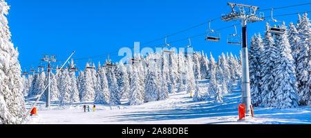 Panorama of ski resort, slope, skiers on the chair lift, white snow pine trees, Kopaonik, Serbia - Stock Photo