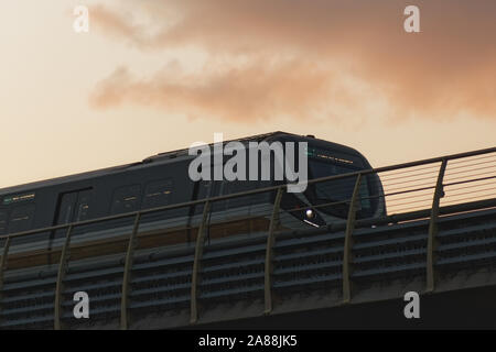 Suburban train with modern desing moving through a bridge with red skyline and sunset clouds in the background. - Stock Photo