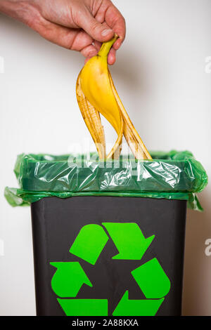 Hand putting banana peel in recycling bio bin. Person in a house kitchen separating waste. Black trash bin with green bag and recycling symbol. - Stock Photo