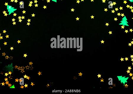 Golden stars and green fir trees glitter on black background. Festive holiday Christmas backdrop. - Stock Photo