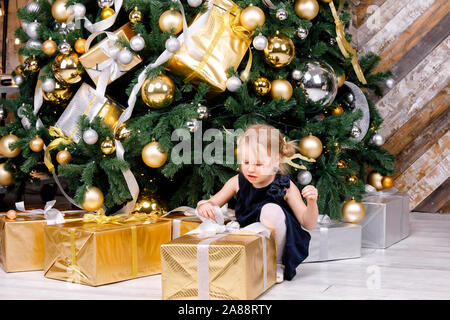Portrait of elementary age girl wearing blue dress sitting beside christmas tree unpacking big wrapped gift box curious about a present on boxing day - Stock Photo