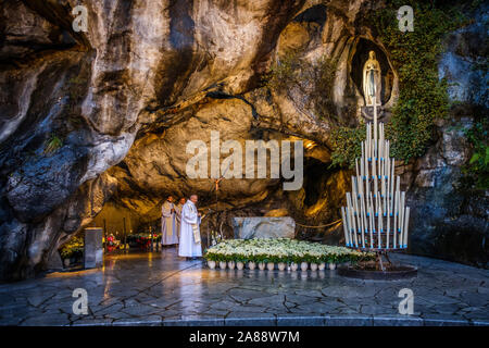 Lourdes (south-western France). Pilgrims at the Grotto of Massabielle, on the banks of the Gave de Pau river - Stock Photo